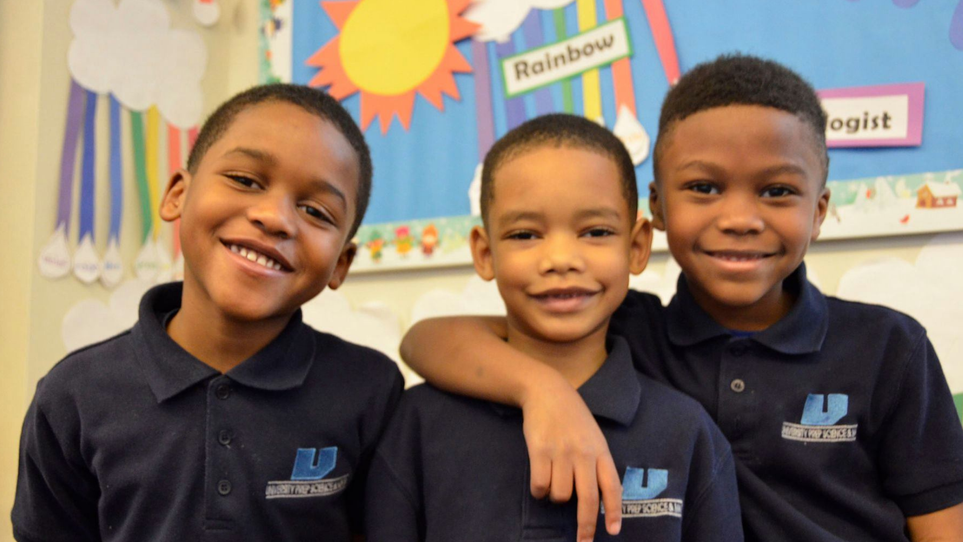 Three male African American students stand smiling at the camera. The furtherest right has his arm around the middle student's shoulders.