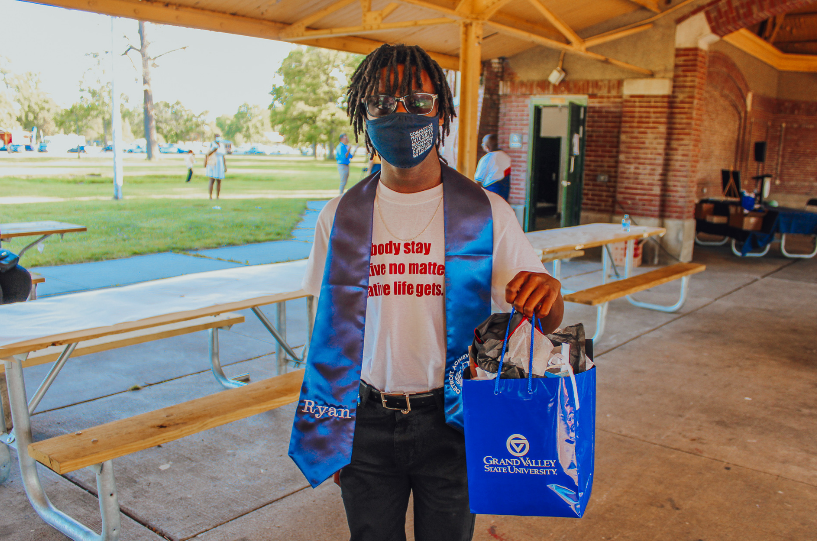 An African America student stands with a Grand Valley State University gift bag