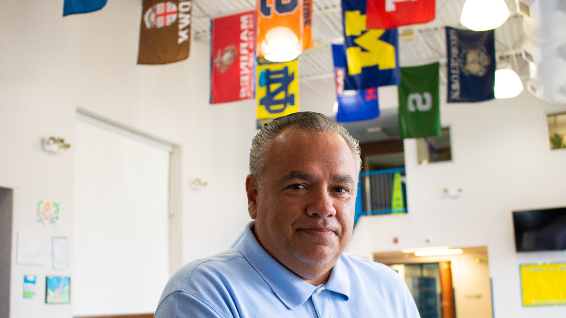 A photo of Cesar Chavez Academy High School Principal, Juan Martinez, posing in the CCA cafeteria, where the flags of many universities hang from the ceiling in the background.