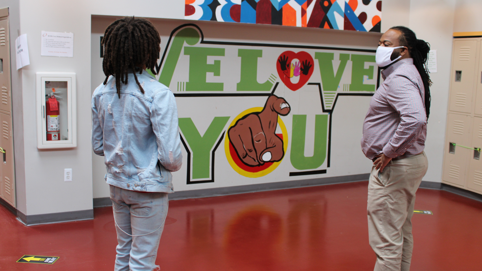 An African American student stands with his back to the camera looking toward a male African American educator. They both face a mural that reads
