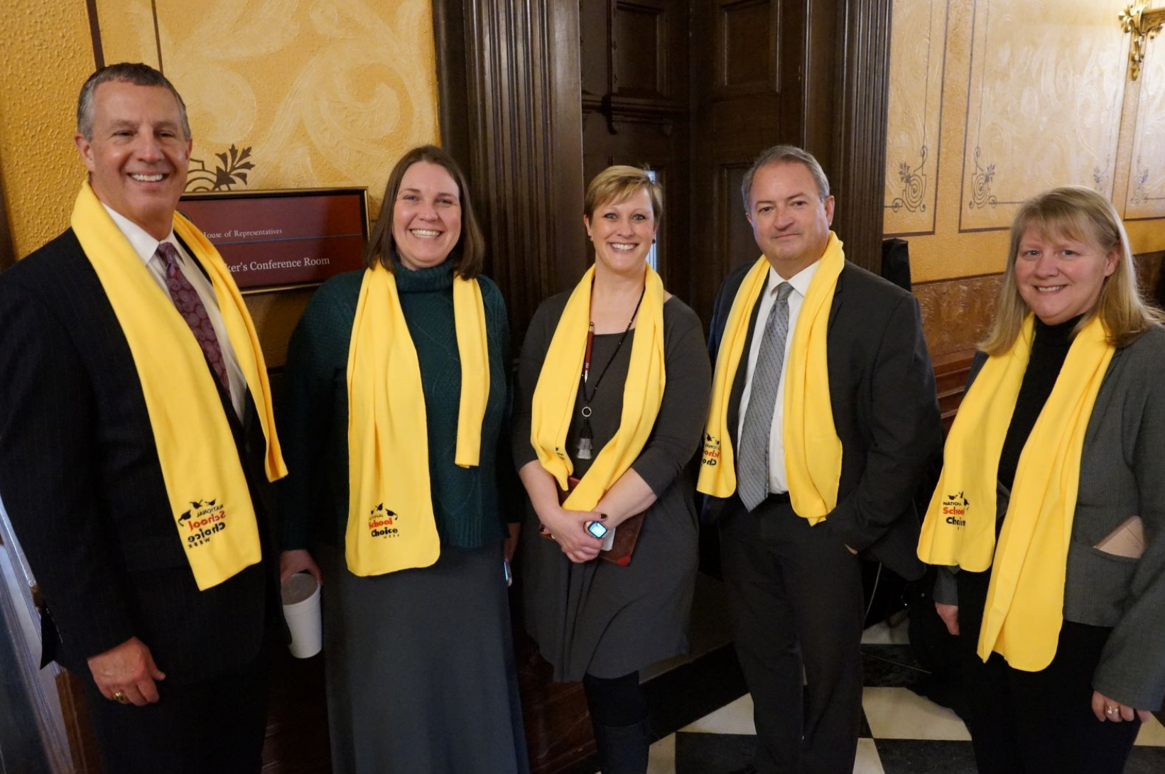 A group of charter advocates stand inside the Michigan state capitol building.