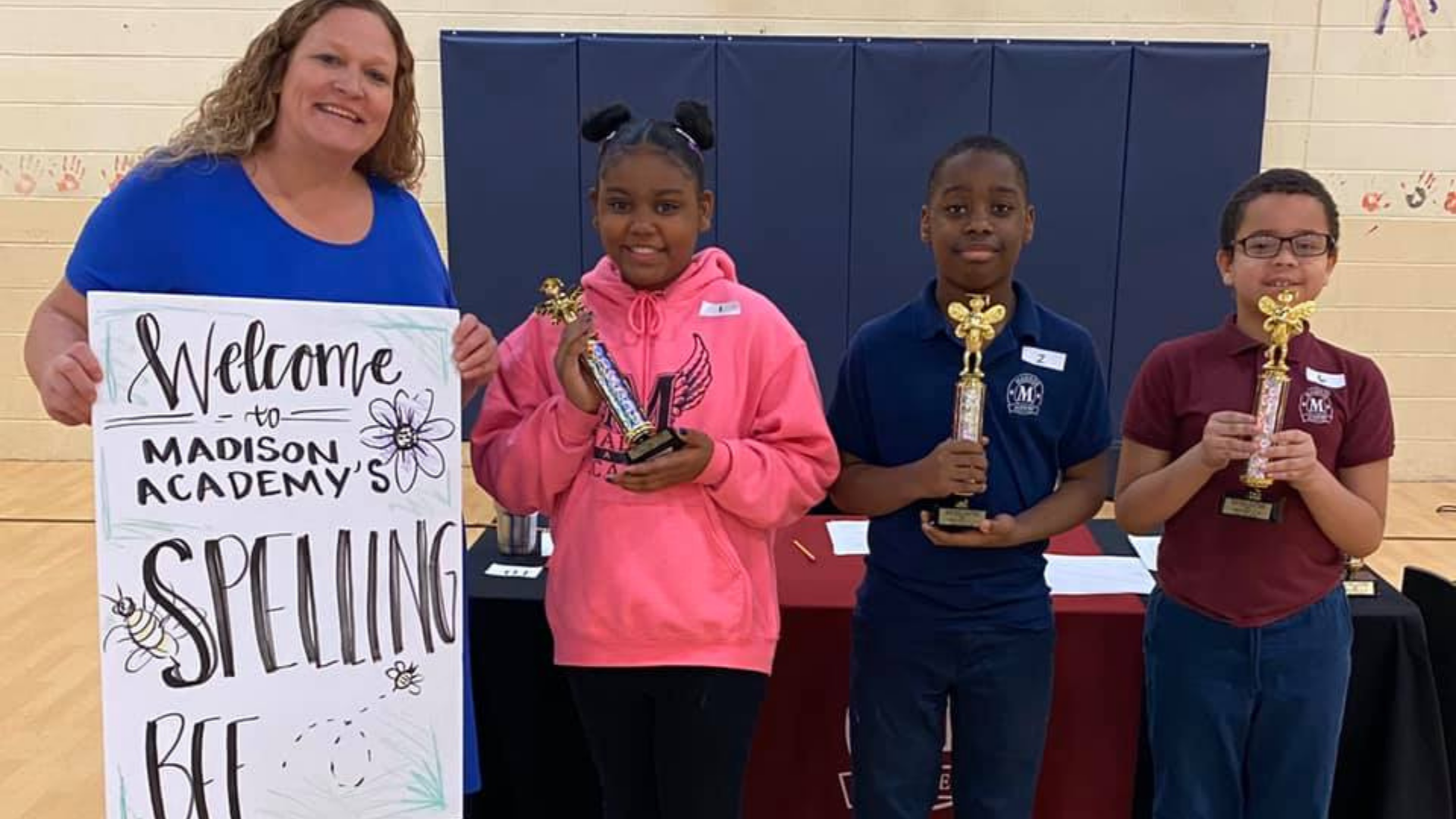 A white teacher stands holding a sign that reads welcome the Madison Academy's Spelling Bee
